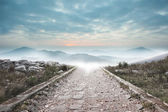 Stony path leading to misty mountain range — Stock Photo
