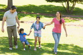 Family of four holding hands and walking at park — Stock Photo