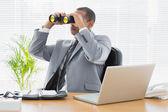 Podnikatel při pohledu dalekohledem na stůl — Stockfoto