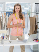 Female fashion designer with laptop and cellphone in studio — Stock Photo