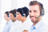 Business colleagues with headsets in a row — Stock Photo