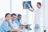 Female doctor explaining x-ray to her team — Stock Photo