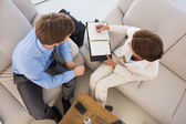 Business team working together on the couch scheduling in diary — Stock Photo