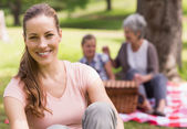 Woman with grandmother and granddaughter in background at park — Stock Photo