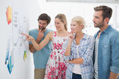 Artists in discussion in front of whiteboard — Stock Photo