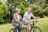 Senior couple on cycle ride in countryside — Stock Photo