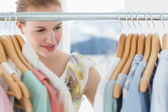 Female customer selecting clothes at store — Stock Photo