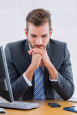 Thoughtful businessman sitting at office desk — Stock Photo