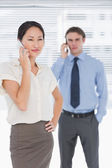Businesswoman and man using cellphones in office — Stock Photo