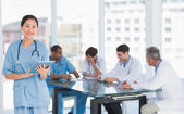 Surgeon using digital tablet with group around table in hospital — Stock Photo