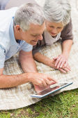 Smiling senior couple using digital tablet at park — Stock Photo