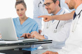 Group of concentrated doctors using laptop together — Stock Photo