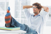 Casual young man with legs on desk in office — Stock Photo