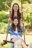 Happy mother pushing daughter on swing — Stock Photo