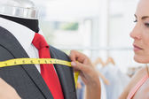 Close-up of a female fashion designer measuring suit on dummy — Stock Photo