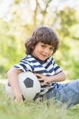Cute little boy with football sitting on grass in park — Stock Photo
