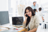 Woman on call at desk with colleagues behind in office — Stock Photo