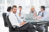 Young businessman with colleagues discussing in office — Stock Photo