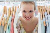 Happy female customer amid clothes rack — Stock Photo