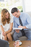 Smiling couple in meeting with a financial adviser — Stock Photo