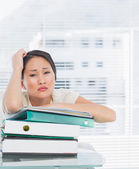 Bored businesswoman with stack of folders at desk — Stock Photo