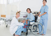Doctors with female patient in wheelchair at hospital — Stock Photo