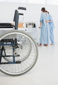 Doctor helping patient to walk with wheelchair in foreground — Stock Photo