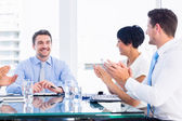 Executives clapping around conference table — Stock Photo