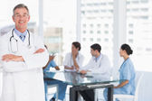 Doctor with group around table in background at hospital — Stock Photo
