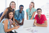 Young casual people using laptop in office — Stock Photo