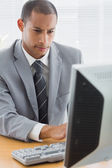 Concentrated businessman using computer at office — Stock Photo