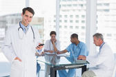 Doctor text messaging with group around table in hospital — Stock Photo