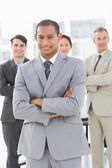 Businessman smiling at camera with team behind him — Stock Photo