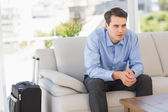 Businessman sitting on couch waiting to leave on business trip — Stock Photo