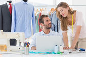Fashion designers using laptop in studio — Stock Photo