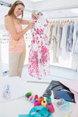 Female fashion designer working on floral dress at studio — Stock Photo