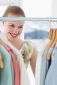 Beautiful female customer selecting clothes at store — Stock Photo