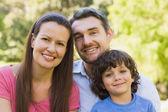 Close-up van een glimlachende paar met zoon in park — Stockfoto