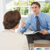 Young businessman scheduling with colleague sitting on couch — Stock Photo