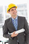 Happy architect smiling and holding blueprints — Stock Photo