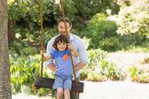 Feliz padre empujando a niño en columpio — Foto de Stock