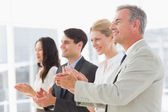 Business team standing in a line applauding — Stockfoto