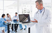 Doctor holding laptop with group around table in hospital — Stock Photo