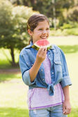 Smiling young girl eating water melon in park — Stock Photo