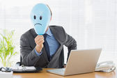 Businessman holding sad smiley faced balloon at office — Stock Photo