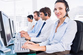Business colleagues with headsets using computers — Stock Photo