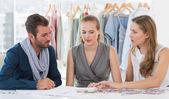 Three fashion designers discussing designs — Stock Photo
