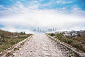 Stony path leading to misty cityscape — Stock Photo