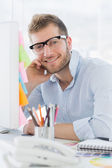 Portrait of a smiling young man using computer — Stock Photo