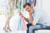 Bored man with shopping bags while woman by clothes rack — Stock Photo